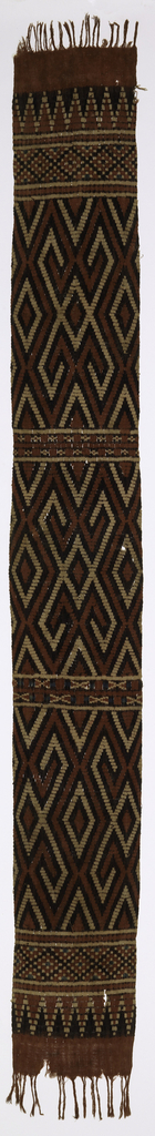 """A long narrow ceremonial fabric (pewo) patterned with a design of interlocking lines forming diamond shapes in red, blue, purple and white. This design, known as """"sekong"""", is thought to represent a geneology--a group of stylized four-limbed people interconnected. It is separated by narrow bands of geometric designs featuring crosses and triangles. Fringed."""