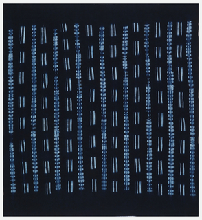 Deep indigo-blue fabric with vertical stripes of dots and dashes in light blue, created by machine-stitched resist. Foundation fabric has a geometric woven damask pattern.