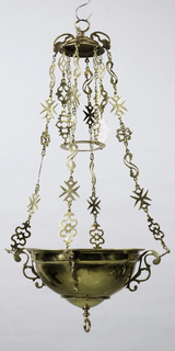 Prefericulum shaped, and suspended by four chains from an inverted bowl. The chains return, and support a round ring which hangs, centered to the main body of the lamp and about ten inches above it. The main body of the lamp is unadorned save for two fillets, a rolled, splayed rim and a ring which is attached to the lowermost point of the lamp. The inverted bowl is decorated by a torus and surmounted by a ring. Four handles in wrought scroll shapes act as brackets for the four suspension chains. The links of the chains are wrought in forms of bucklers, Maltese crosses (eight-point crosses), clefs, rampant lions, each connected by small eight-shaped links.
