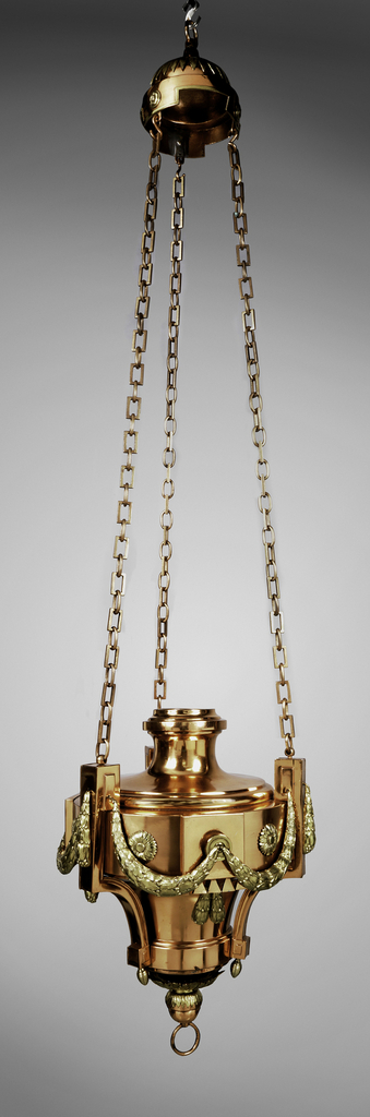 Hanging lamp with helmet-like cover and starburst over it; from it three chains, composed of square links, is suspended a light that is rounded and decorated with garlands, terminating in a knob and a ring.