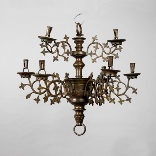 Nine-armed chandelier; six arms on lower section, three above. Central baluster shaft. Arms are cast and chased in pattern of scrolling foliage; with flat drip pans and open sockets.