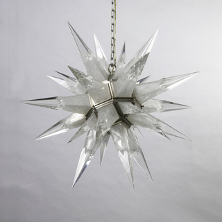 Glass hanging lamp in the form of a many-pointed star, the points of varying lengths. Each point cut and etched with angular geometric patterns. Housed in a metal strapwork frame suspended from a metal chain.