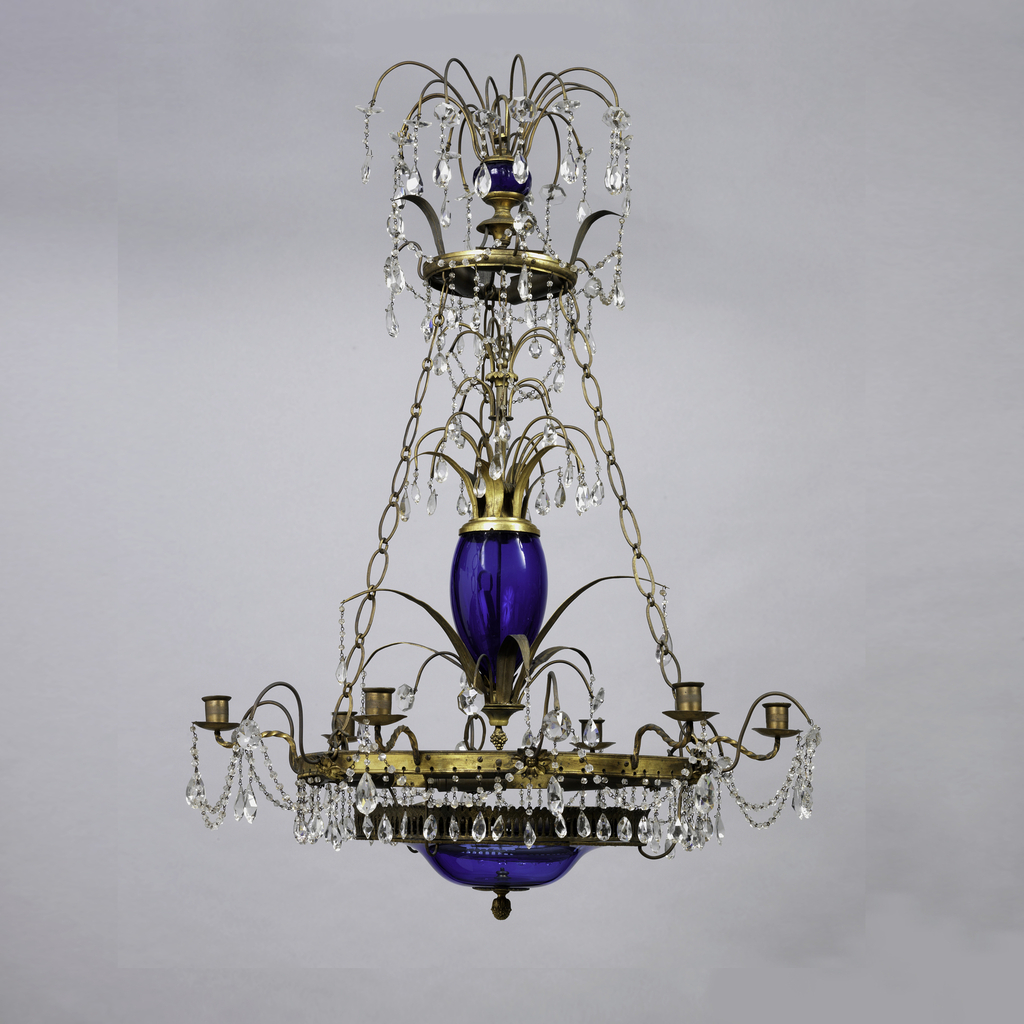 Three tiers of graceful fountains of glass descend from the top, set off by swags of glass drops, the blown glass stems delicately engraved; gilt lower ring with six candle arms and an upper ring connected by the glass-surrounded stem and by three chains, all of metal, the lower ring supporting a blue glass disc at the base of the stem.