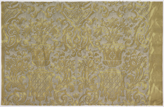 The ground fabric has a marbled effect in shades of ochre, possibly achieved with a partial discharge technique, overprinted with silver metallic ink in a pattern of urns with foliage.