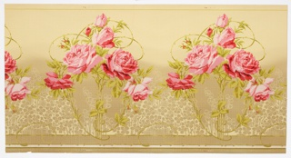 Clusters of large pink roses on scrolling vines. Towards bottom of frieze are petite flowers printed in silhouette, creating a lace-like effect. The background shades from light tan at the top to a deeper gray color at the bottom.