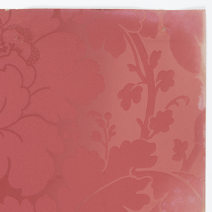 Damask-like design. All-over pattern of large pink flowers on vines. Printed on lighter pink background.