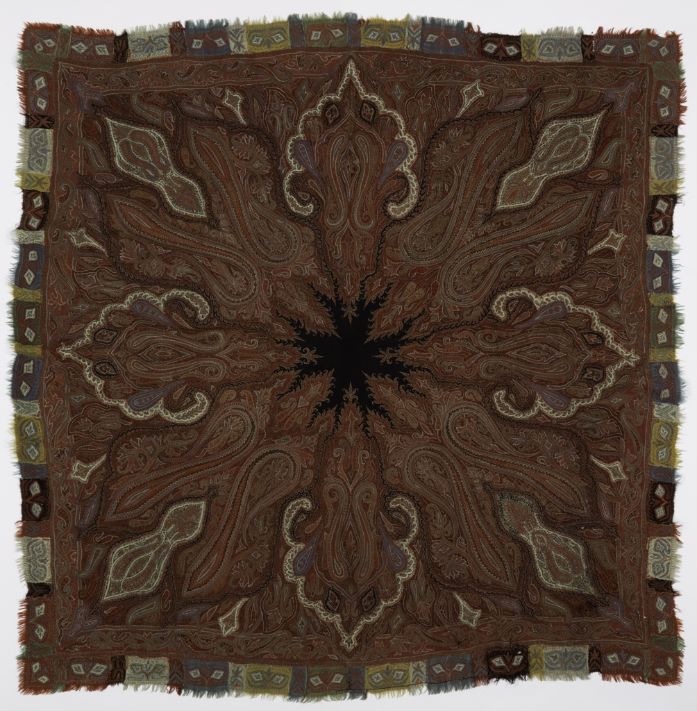 "Square shawl with a solid black center medallion and a vertically and horizontally symmetrical design of elongated boteh or paisley forms incorporated into an overal vegetal scheme.The shawl is embroidered in a design typical of woven-pattern Kashmir shawls in red, white, blue, black and green threads on ground of red twill. The black twill which forms the center medallion is pieced in, while small solid areas of red, black and blue cloth are appliquéd. Guard border and separate ""harlequin"" border of green, blue, yellow, white, red and black tabs. Signature in center."