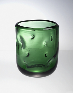 Transparent green glass with circular impressions on surface.