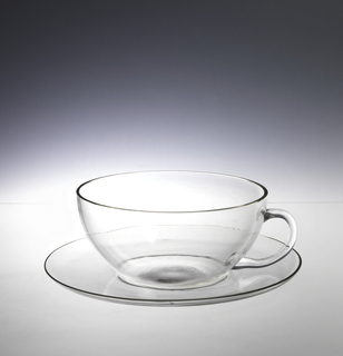 Shallow hemispherical cup, loop handle.  Concave circular saucer.