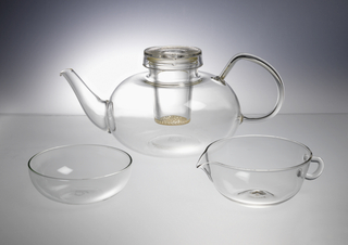 Clear mold blown glass. (a) flattened globular body, flattened base; applied curved, tapered spout; applied solid curved handle, with flattened section at upper juncture; collar neck. (b) Infuser, tapered truncated cone with pierced bottom and collar to rest on neck of teapot. (c) cover molded with concentric rings and three strust to rest on infuser.