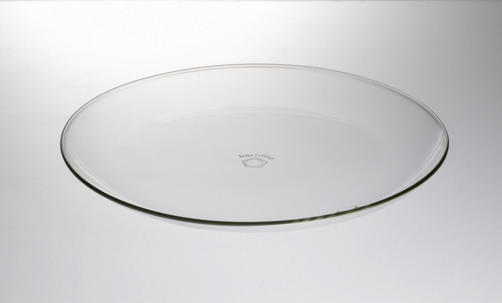 Clear glass circular plate with curved edge; flat base.