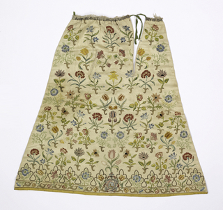 Skirt front panel of ivory silk satin, seamed down the center front, with a slit for a pocket and a tie closure. Embroidered in polychrome silks with various flowers including tulip, rose, carnation, columbine, and others, with stems worked in silver and gold thread. Border at bottom of scalloped shaped frame to flowers worked in gold thread. At the center bottom, a shield-shaped medallion framed by feathers and with a plumed helmet at the top; inside the medallion is a bull with a star above his head. At the top edge, silver lace and soft ruching, and the remains of green raw silk tie tapes; lined with white linen.