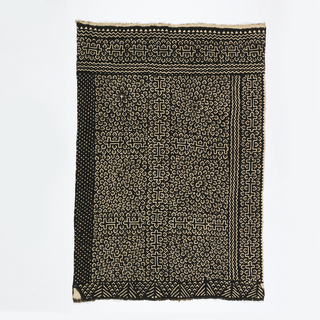 "Woman's wrapper consisting of eight 5 1/2 inch wide strips of handwoven cotton, sewn together to make a panel. The center field is divided into six squares separated by bands of H-shaped ""airplane"" motifs. Each square is patterned with incomplete diamonds with a dot in the center, radiating out from a center dot in a petal-like arrangement. The outer and lower borders  use the same motifs as the center field. The upper border (when worn, seen here on the left) has scattered white dots. The inner border (when worn) interlocking triangles.  With guard borders of narrow zigzags. Design is reserved in white on a dyed brownish-black ground."