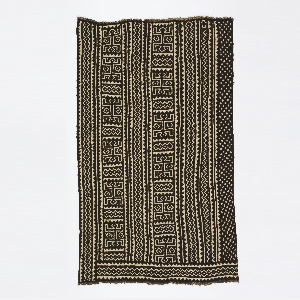 A  woman's wrapper consisting of seven strips, each five-inches wide, sewn together to make a panel. Columns of pattern include the crocodile motif, along with dots and zigzags. The upper border (when worn, seen here on the right) has scattered white dots. Design is reserved in white on a dyed brownish-black ground.