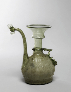 Light green; vessel with long flaring neck and slightly pear shaped body with tear drop shaped relief along base. One handle of applied glass and long upturned spout.