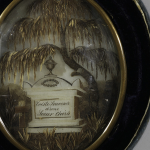 "Oval brass form surrounding scene made of hair, depicting tomb monument topped by urn and inscribed: ""Triste souvenir d'une soeur cherie."" Tomb flanked by tufts of grass with a weeping willow tree behind, all under a domed glass cover.  Mounted in blue-green velvet covered oval case, interior covered in grey-green velvet."