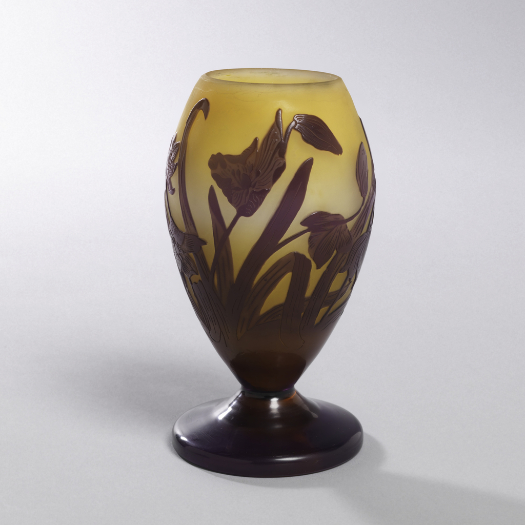 Footed glass vase with dark applied decoration of plants (silhouette-like) on yellow background.