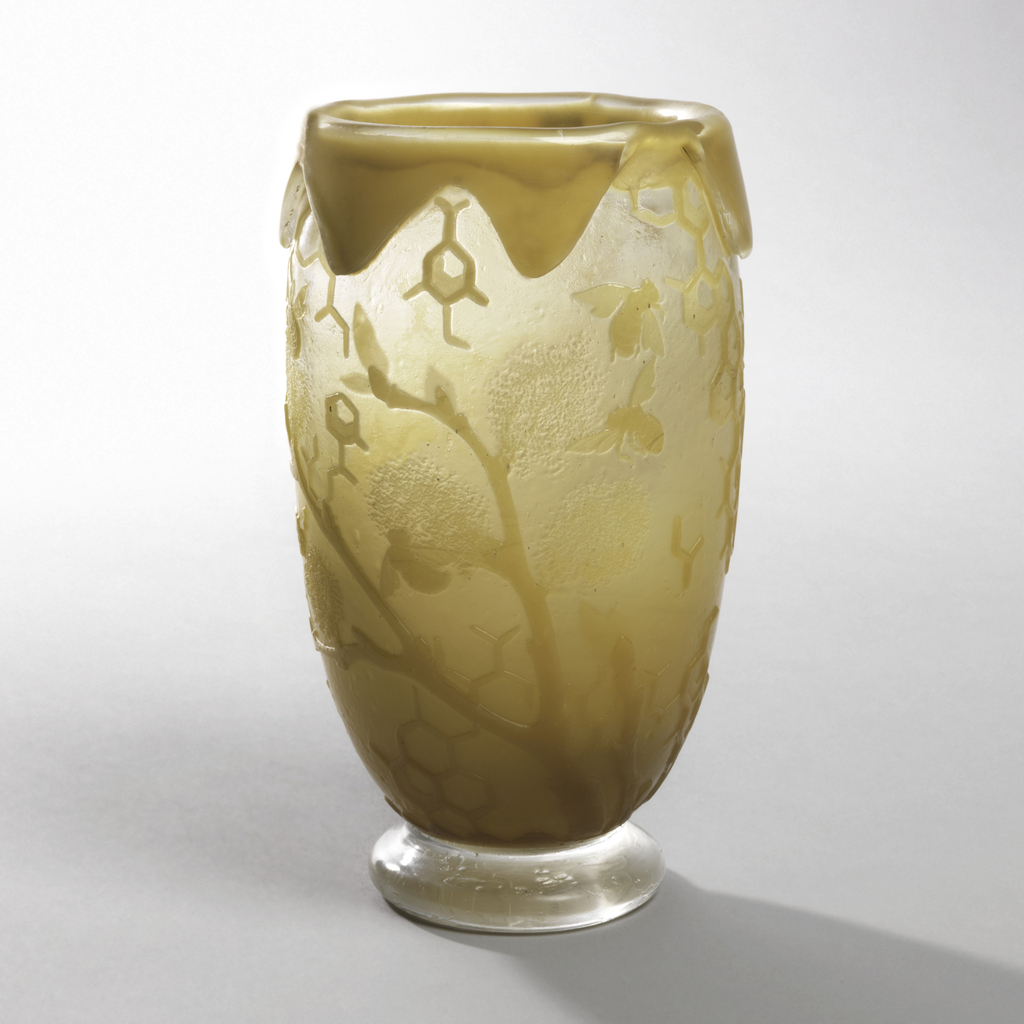 """Ovoid footed vase with honey-colored depiction of honeycomb pattern and bees. Rim with overflowing """"honey""""."""