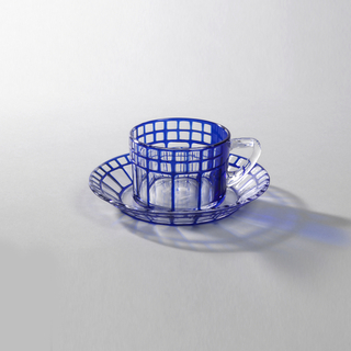 Circular cup (a) and saucer (b) of clear glass flashed with blue cut back into a regular geometric lines delineating clear squares and rectangles. Clear handle on cup.