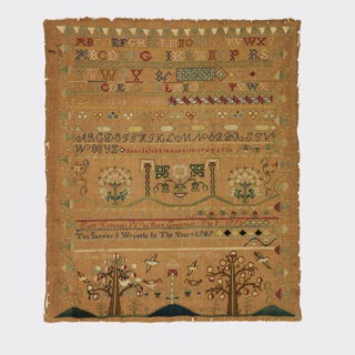 Embroidered sampler with bands of alphabets and numerals, floral and geometric borders, and an inscription. At the bottom are two trees, one surrounded by birds, the other with birds flying away from it; the trees are identified as 'The Good Tree' and 'The Evil Tree'. The verse reads:   Let Virtue be a Guide to Me When this you see Remember Me