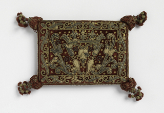 Small flat rectangular cushion of red velvet embroidered in flat gold, gold thread and sequins with silks and metal tassels at the corners. Pattern of a coronet at center supported by and flanked by stylized foliage. Narrow border of S-curves.