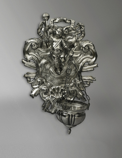 An angel stands upon clouds in front of a scrollwork escutcheon with a glory of rays. He holds an aspergillum in his raised right hand, and the bowl in his left. The bowl is suspended on three chains which are fastened to cherubim who are applied to the brim of the bowl.