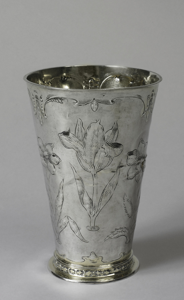 """Flaring body with large vertically arranged stemmed flowers, repoussé and stippled. Scrolled band in """"Ohrmschel"""" style at top and bottom. Foot ring in lozenge pattern above flat foot, gilt as is the inside."""