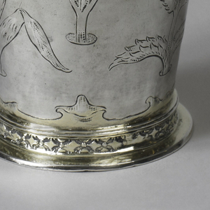 "Flaring body with large vertically arranged stemmed flowers, repoussé and stippled. Scrolled band in ""Ohrmschel"" style at top and bottom. Foot ring in lozenge pattern above flat foot, gilt as is the inside."