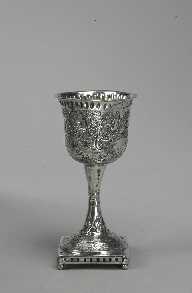 Square openwork base on four ball feet. Domed foot, hourglass-shaped stem and bell-shaped cup decorated with engraved and stippled scenes of rabbit-hunting dogs among large flowers and foliage. On edge of cup repoussé band of vertical ovals.