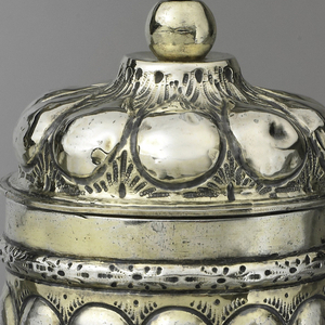 repoussé pineapple pattern on cup(a) and lid (b), with parcel-gilt band at connection, above a lobate stem and foot. Cover finial is gilt silver ball secured to cover by pin with small round silver head.