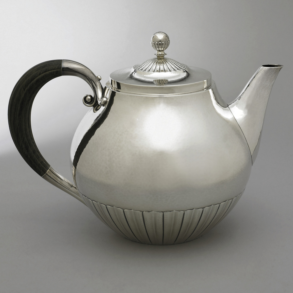 Silver bulbous teapot; lower section with vertical ribs, looped ebony handle. Plain spout and scalloped lid, finial with lower section ribbed and scalloped.