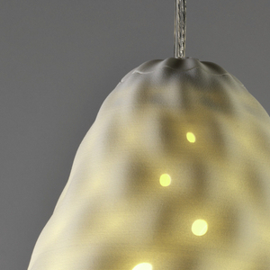 White, irregular ovoid form with diagonal striations and small holes throughout; bulb housing at top, suspended from clear plastic-coated cord.