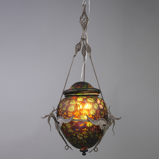 Lamp composed of ovoid form glass globe made of thirteen different multi-colored murrines, leaves and rod canes in mosaic technique, set into a manganese colored ground on a clear under ground base, with a cobalt blue finial at the base, surmounted by a domed cap with nine different murrines, leaves and matching ground color, with a hole in the top for an electric wire; the globe surrounded by a polychrome decorated incised wrought iron band with three-winged dragons where rods with spiral twist tops join the structure to the hanging rod.