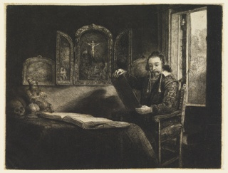 A man is seated before a table, facing left, holding a print in his hands, with back against an open window.  A book and other objects are on the table, pictures on the wall include a triptych with the Crucifixion as the subject of the central panel.