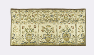 Three complete panels and two half-panels in an embroidered design showing a border of scrolling stems and flowers above birds and flower sprays placed at either side of a vase with flowers. Two cross borders show pendant flowers set in scallops. Bordered with gold thread trimming.