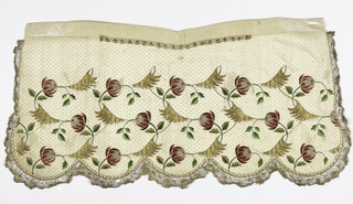 Cream white apron embroidered in colored silks and gold and silver thread. Design shows three offset rows of heavy rose buds with curving stems and leaves. Between each rose bud is a heavy drooping leaf in gold thread. Apron has five scallops along the bottom and is trimmed on three sides with metallic bobbin lace. A narrow piece of bobbin lace is at the top. Apron has a yoke of plain silk and drawstring.
