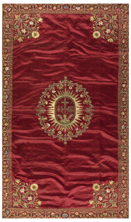 Hanging of dark red silk embroidered along all sides with a border showing a floral pattern in metallic thread and multicolored silk. Center shows an oval-shaped sun filled a pierced heart and other symbolic devices.