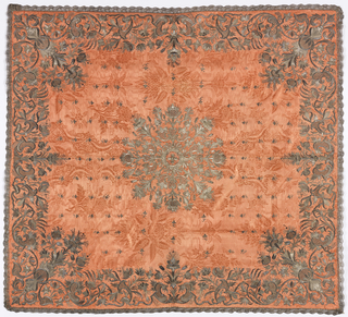Cover with metallic threads on an dark orange foundation in a vertically symmetrical pattern of flowers with continuous frame at the left and right sides. Floral medallion in center and floral border symmetrical in corners and center of each side. Bobbin lace on four sides.