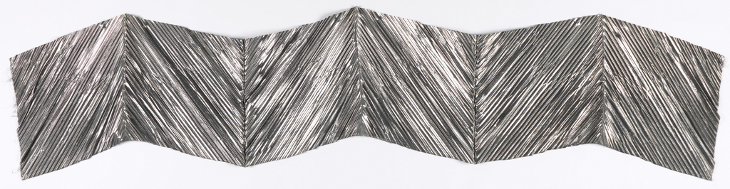 Silver metallic fabric, folded and pleated to create a zigzag design.