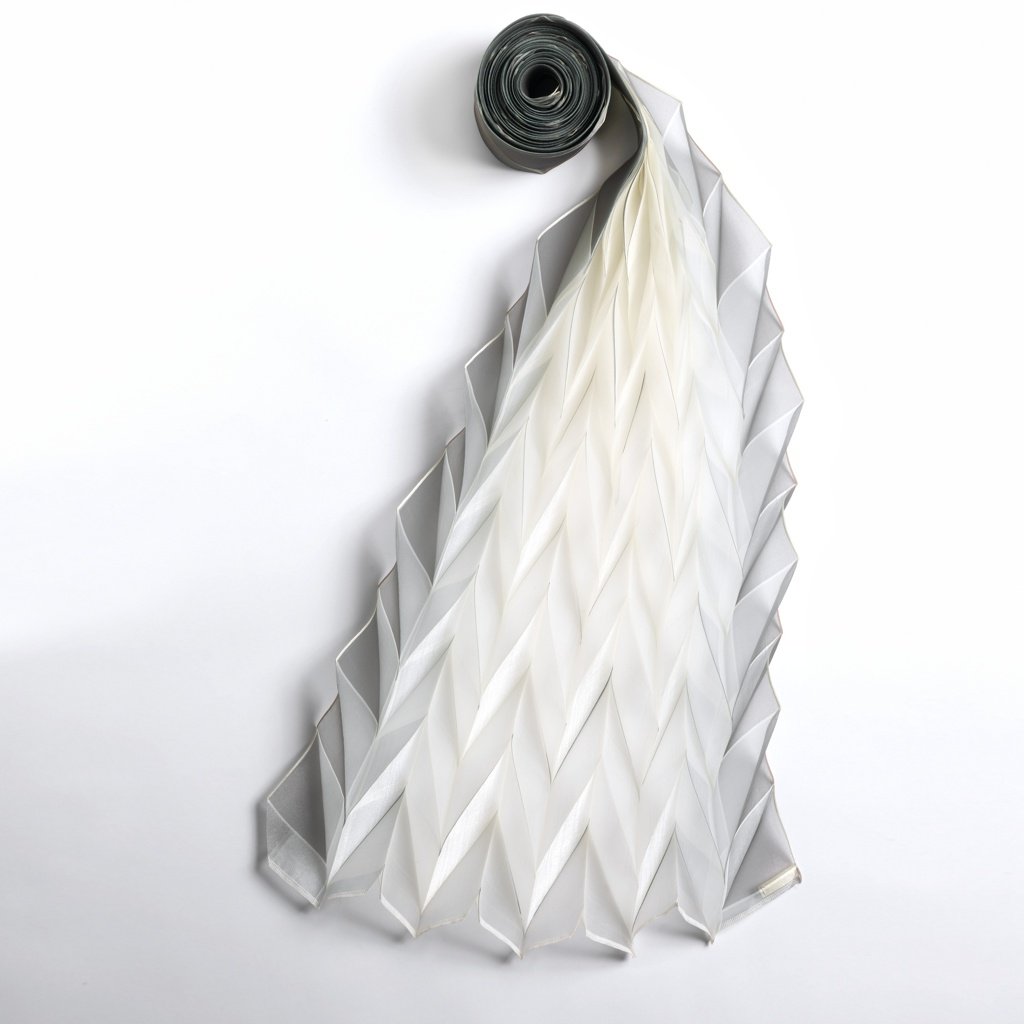 Long length of polyester which is folded in the 'mountains and valleys' origami pattern. Pieces of dye transfer paper are inserted between the folds at the edges. The folds are permanently pressed in and the dye transfer effected in one step. The dye permeates the folds to varying degrees.