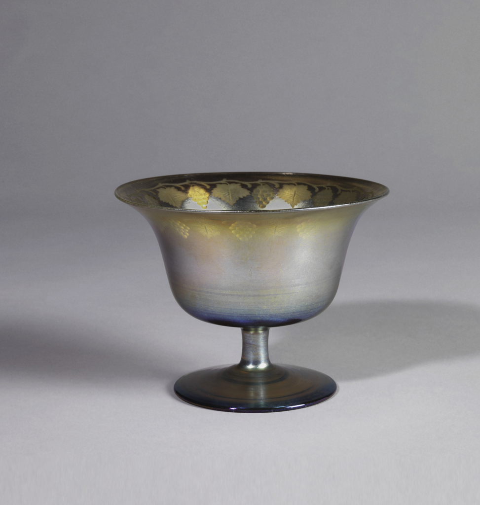 Spreading foot and short plain stem support bowl flaring to lip - iridescent - engraved band of symmetrical vintage motifs about inside upper margin.