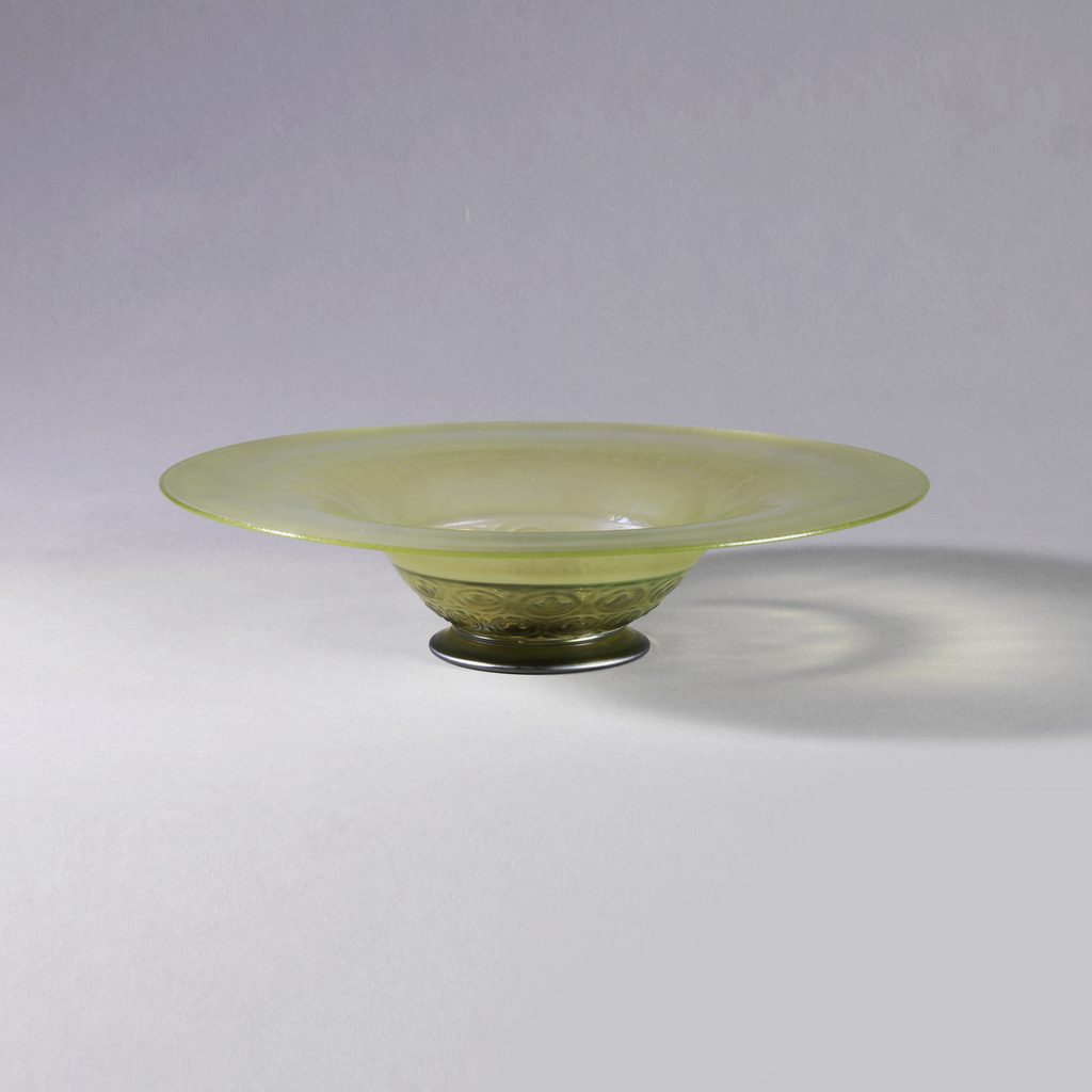 Pale gold metallic luster on exterior of transparent glass, forming band of spectral colors around inner portion of broad, flat rim; relief band on lower exterior of bowl consisting of two rows each containing twelve round designs on blister-like background; low foot.