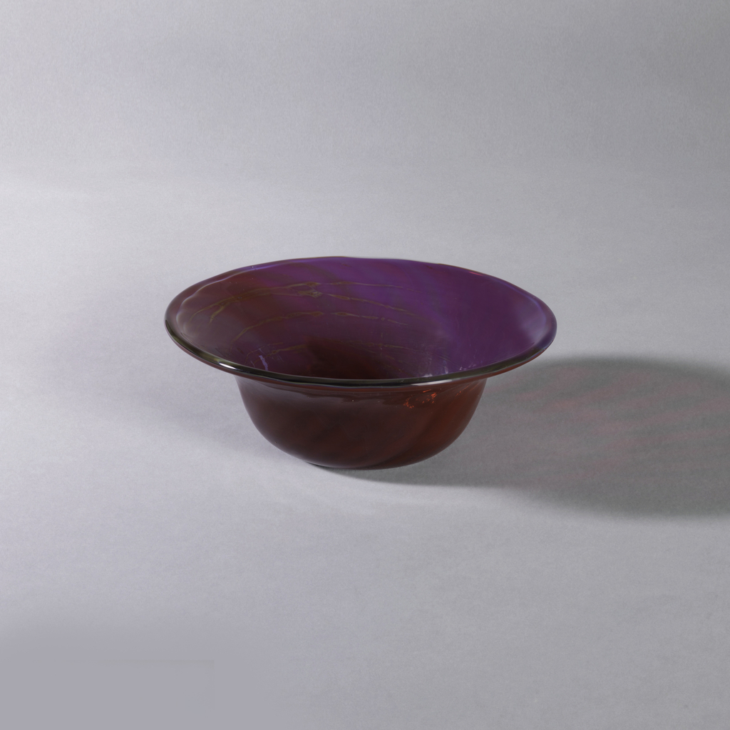 Transparent ruby red with interior of slightly milky multicolor iridescence giving lavender and greenish-blue effect; spiral pattern; deep bowl; flaring rim.