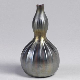 Gray metallic luster on ribbed gourd-shaped body. Opaque white glass inside lip and probably most of interior.