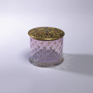 (a) Straight sided round jar of transparent pink glass with milky diaper pattern; stylized floral pattern in base; transparent flat foot. (b) Slightly convex brass lid with threaded design partially enameled in red, green, blue; projecting narrow lip.