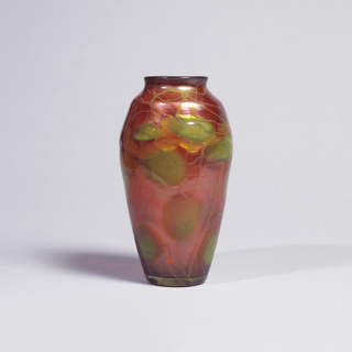 Tall vase in iridescent red orange, milli-flore (green leaves) motif.
