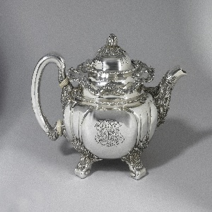 Teapot of squat globular form with reeding, wavy rim, curved handle with ivory insulators, spout with chrysanthemums and foliage; base with four foliate feet; domed and reeded hinged lid with flower bud knop.