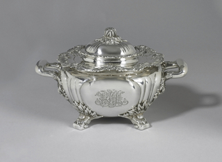 "Squat globular form engraved with foliate monogram ""RMA"", with reeding, wavy rim, two squared, curved horizontal handles with foliate decoration; base with four foliate feet; domed and reeded lid with flower bud knop."