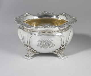 "Squat globular form with reeding, engraved with foliate monogram ""RMA""; wavy rim with foliate decoration; base with four foliate feet."