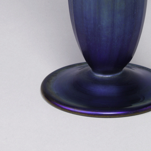 Long tall cylindrical and footed vase in iridescent purple to green glass.